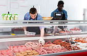 Skillful butcher with colleague working behind counter