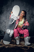 Female in a pink snowboarder costume holding snowboard.