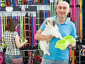 Adult man with dog looking bowl in pet store