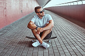 Portrait of a handsome fashionable skater guy in sunglasses dressed in a white shirt and shorts sitting on a skateboard under a bridge, looking away.