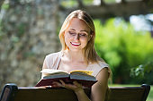 young woman on bench reading book