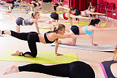 Girls perform exercises on yoga, lying on mat