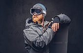 Brutal redhead snowboarder with a full beard in a winter hat and protective glasses dressed in a snowboarding coat posing with snowboard at a studio, looking away. Isolated on gray background.