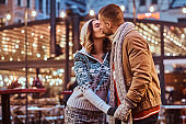 A young romantic couple wearing warm clothes holding hands and kissing standing outdoors at night, enjoying spending time together.