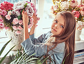 Portrait of a cute little girl with long brown hair and piercing glance wearing a stylish dress, posing with flowers against window at home