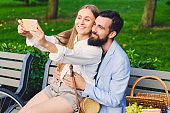 A couple on a date make selfie in a park.