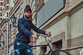 Portrait of a fashionable man in stylish clothes walking with city bicycle on the street.