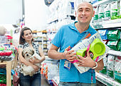 Positive man with purchases in pet store, female on background