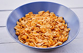 Corn flakes in a plate on a wooden desk.