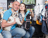 Smiling couple choosing for new clothes for dog