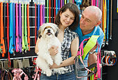 Young family couple with dog  choosing new bowl