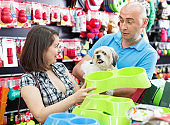 Portrait of smiling couple purchasing new pet bowls in pet store