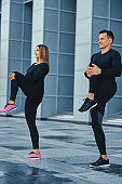 Fitness couple is stretching over modern building background.