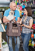 Couple with dog looking transportation box in pet store