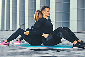 Fitness couple is exercising over modern building background.