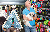 Portrait of young man  with small dog standing  in pet store