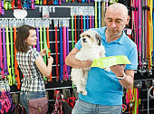 Positive man with dog looking bowl in pet store