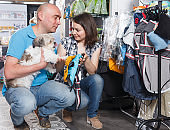 Adult couple choosing for new clothes for dog