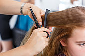 Hands of hairdresser making hairstyle for girl
