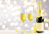 New Year's Eve party with champagne bottle and golden streamers in front of a bokeh background