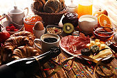breakfast on table with bread buns, croissants, coffe and juice on new years eve
