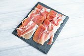 Ham on slate plate on wooden table. Typical tapa of Spanish gastronomy. Food