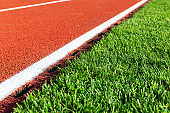 Red running track and green grass field at the sport stadium