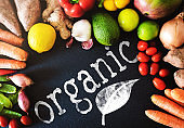 directly above closeup of fresh organic vegetables and fruits on on slate background with word ORGANIC