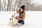 Woman and a dog playing in the snow