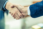 concept of a reliable partnership: a handshake of business partners on blurred light background