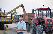 Farmer standing in field with combine harvester and tractor in background