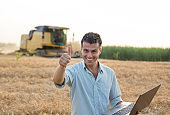 Engineer standing in field with combine harvester in background