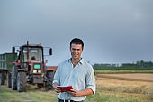 Farmer standing in front of tractor in field