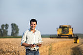 Farmer standing in front of combine harvester in field