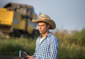 Farmer with tablet standing in front of combine harvester