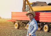 Farmer standing in front of combine harvester