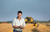 Engineer with note book and combine harvester in field