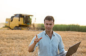 Engineer with laptop and combine harvester in field
