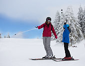 Mother and son with ski equipment in mountains