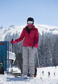 Woman with ski equipment in mountains