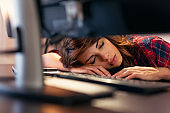 Exhausted woman asleep at her desk