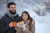 Young couple with hot drink on snow