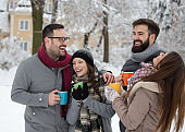 Group of friends drinking hot coffee on snow