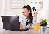 Woman using credit card online at home