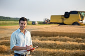 Farmer with notebook in front of combine harvester in field
