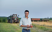 Farmer with notebook in front of tractor in field