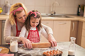 Mother and daughter using a rolling pin