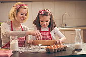 Little girl using rolling pin in the kitchen