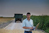 Farmer with laptop in front of tractor in field