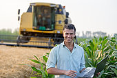 Farmer with laptop in front of combine harvester in field